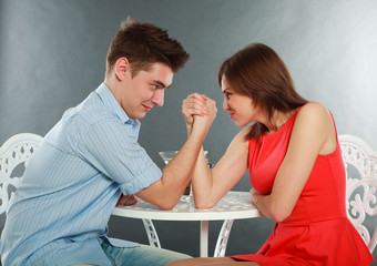 Young happy couple challenge fighting in arm-wrestling at table