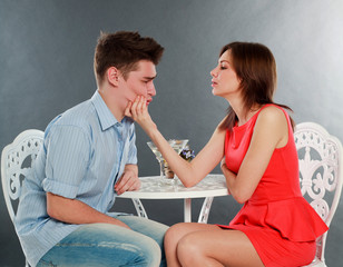 Girl with her drunk and sad boyfriend at table, in studio