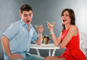 Laugh and drunk couple with glasses of champagne at table