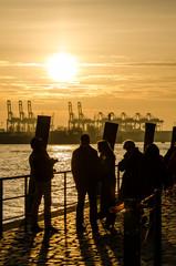 Männer und Frauen bei Elbe schauen auf Containerhafen