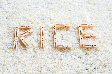 "wooden clothes peg Arrange the words ""RICE"" on rice background"