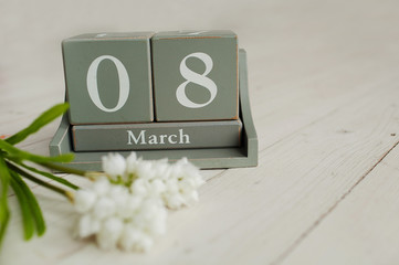Wooden calendar with 8 March and floowers on white background