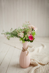 Spring flowers in pink vase on white background