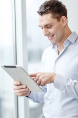 smiling businessman with tablet pc in office