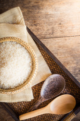 rice in bamboo basket and wooden spoon on sack bag and wooden ba