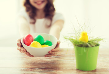 close up of girl holding bowl with colored eggs