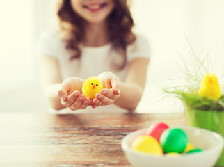 close up of girl holding yellow chiken toy