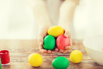 close up of girl holding colored eggs