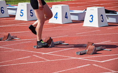 Woman at the starting line of the running track