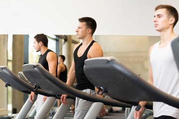 group of men exercising on treadmill in gym