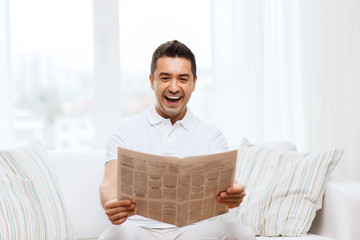 happy man reading newspaper and laughing at home