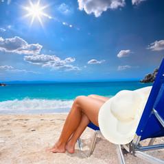 Beautiful woman leg with sunhat  on beach.