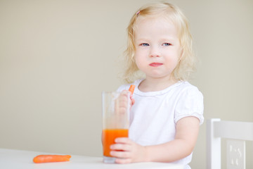 Adorable toddler girl drinking carrot juice
