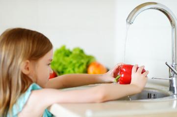 Adorable little girl washing vegetables