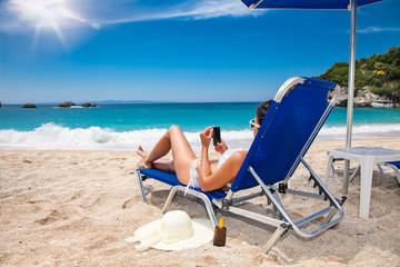 Beautiful woman with phone  in sunhat  enjoying on beach.