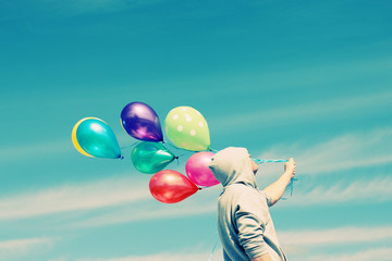 Man holding colorful balloons outside