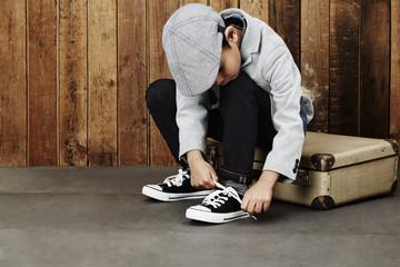 Boy tying shoelace on case