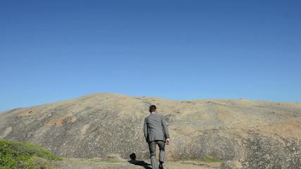 Businessman walking up a hill