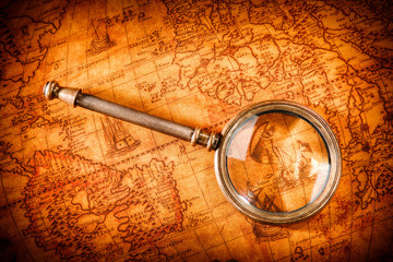 Vintage magnifying glass lies on an ancient world map