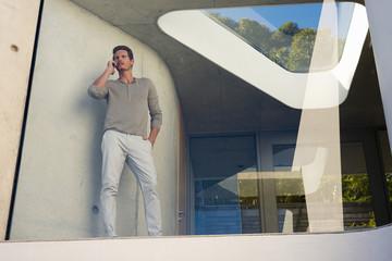 Man phoning behind window