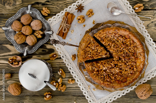 Fototapeta Piece of apple pie with walnut and sugar glaze