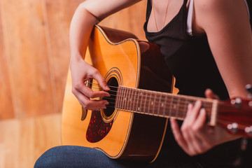woman's hands playing acoustic guitar, close up
