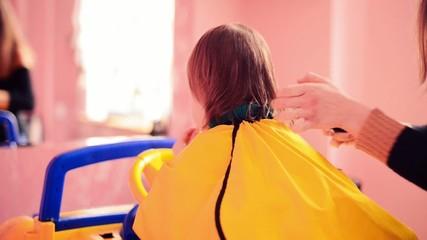 stylist making haircut to a little boy in salon