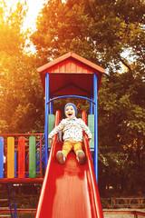 Little boy playing on children's slides