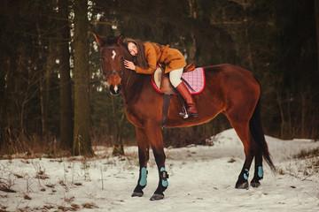 brunette walking outdoors on the horse. Winter park.