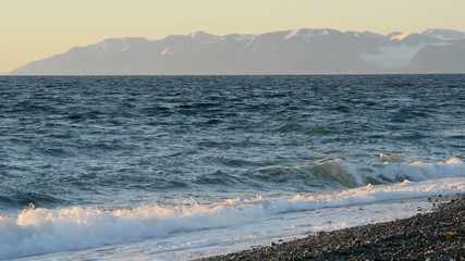 Spitzberg beach with snow covered mountains