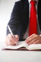 手帳にメモを記入するビジネスマン