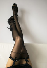 Long Woman legs in stockings on sofa, with high heels.