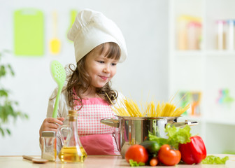 Cook kid makes healthy vegetables meal in the kitchen