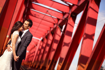 Bride and groom celebrating on a red bridge