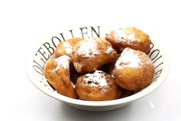 freshly baked traditional dutch oliebollen with powdered sugar