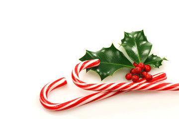 Christmas candy canes with a branch of holly