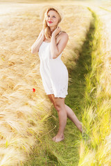 Lonely beautiful young blonde girl in white dress with straw hat