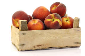peaches in a wooden crate on a white background