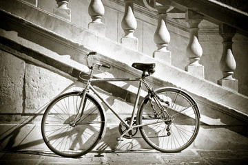Old bicycle against a marble wall (Tuscany - Italy)