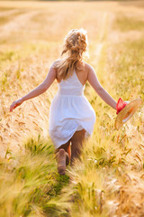 Happy young blonde girl in white dress with straw hat running th
