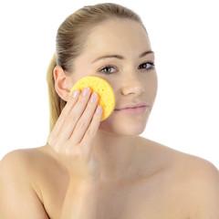 Frau reinigt Gesicht mit Pflege-Schwamm