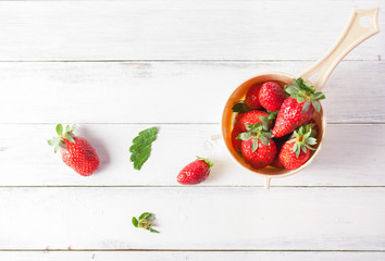 Fresh strawberries in strainer on white wood background