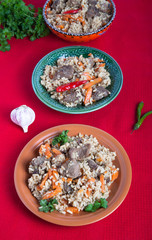 Three plates of hot delicious pilaf with garlic and parsley on r
