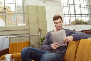 entspannter mann liest die zeitung
