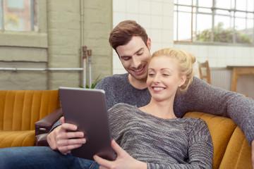 modernes junges paar mit tablet-pc auf dem sofa