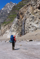 Tourist with a large backpack looks at highest waterfall