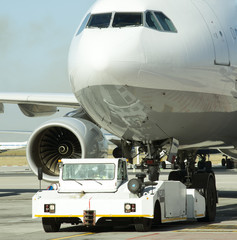Tug moving a passenger jet