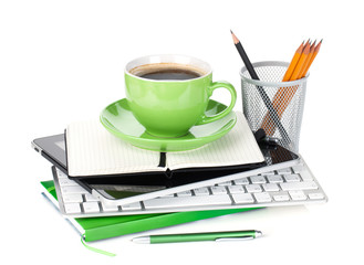 Green coffee cup on office supplies