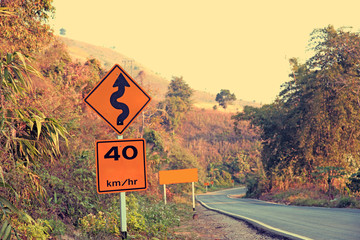 sharp curve road sign beside mountain road