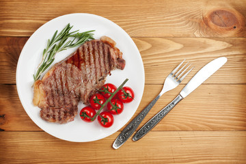 Sirloin steak with rosemary and cherry tomatoes on a plate